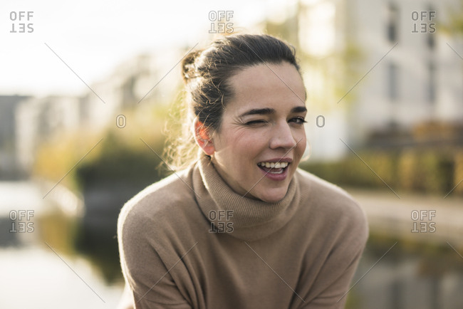 Portrait of winking woman wearing light brown turtleneck pullover in autumn