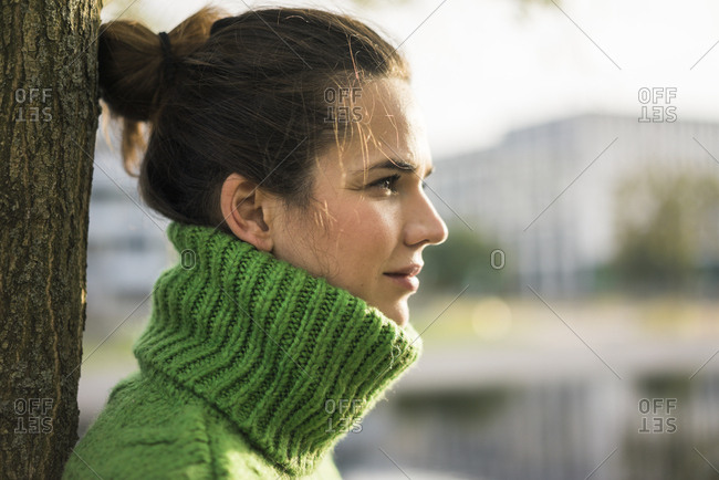 Profile of relaxed woman wearing green turtleneck pullover leaning against tree trunk