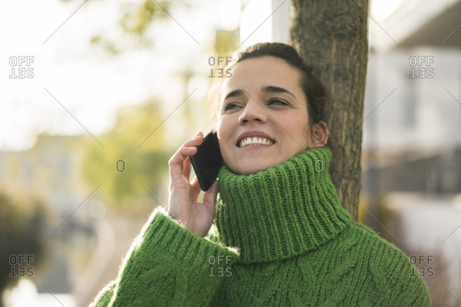 Portrait of happy woman on the phone wearing green turtleneck pullover in autumn