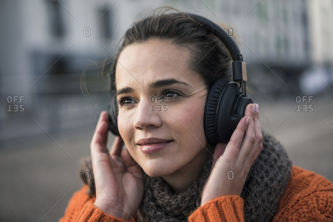 Portrait of smiling woman wearing listening music with cordless headphones in autumn