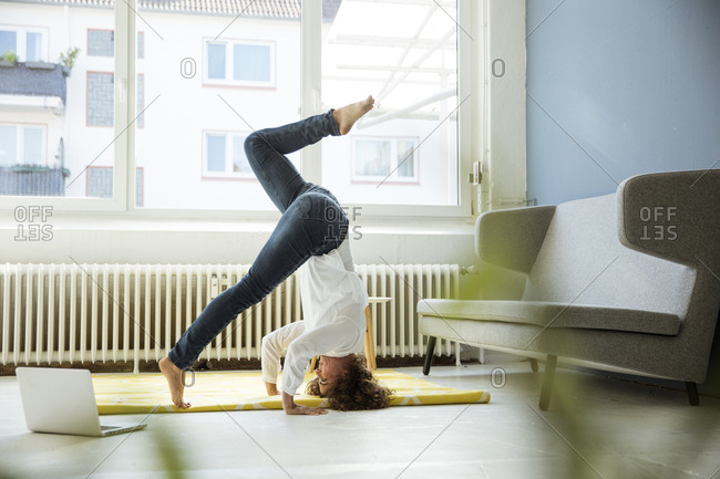 Businesswoman practicing yoga on the floor