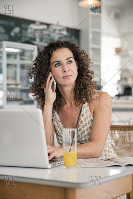 Mature woman sitting in coffee shop- using laptop- talking on he phone