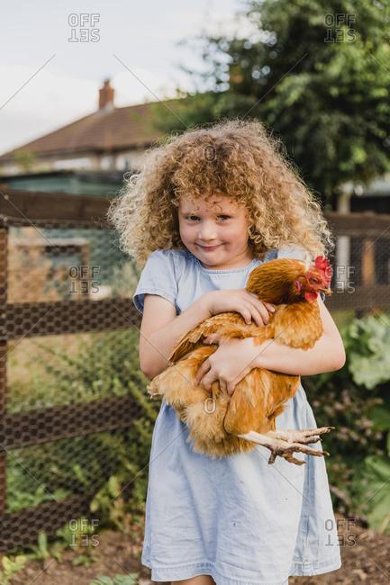 Smiling girl hugging hen