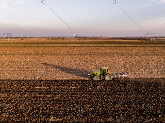 Serbia- Vojvodina. Tractor plowing field in the evening