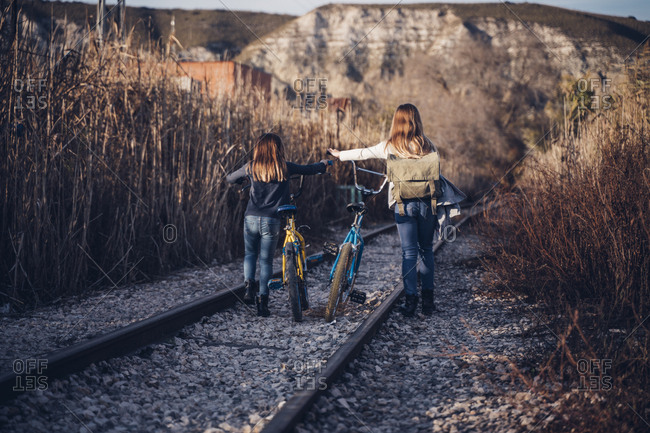 Two girls walking on the train track with bicycles