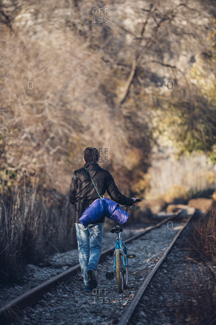 Boy walking on the train track with bicycle