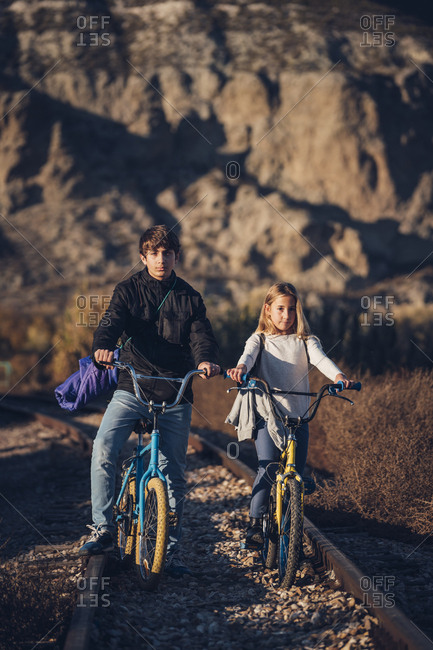 Boy and girl on the train track with bicycles