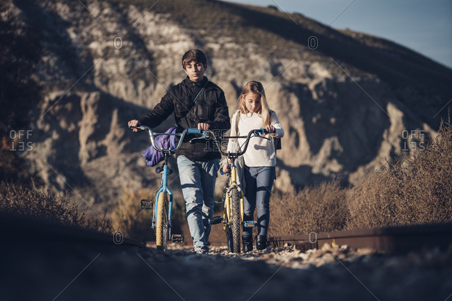 Boy and girl walking on the train track with bicycles