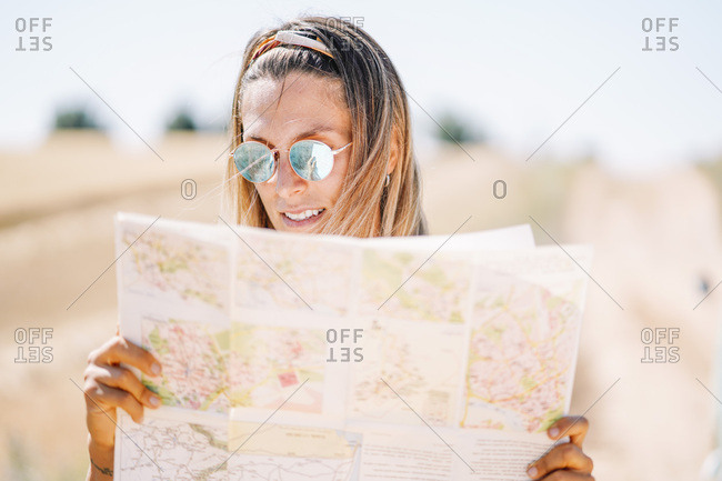 Blond young woman wearing mirrored sunglasses orientating with map