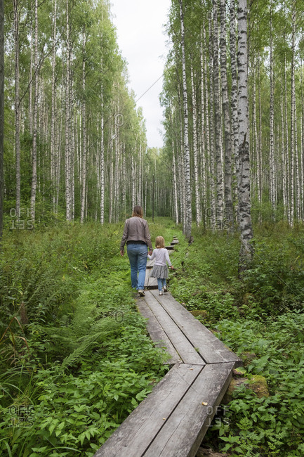 Finland- Kuopio- mother and daughter walking in a birch forest