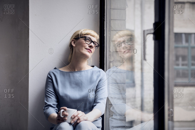 Portrait of smiling woman with coffee mug looking through window