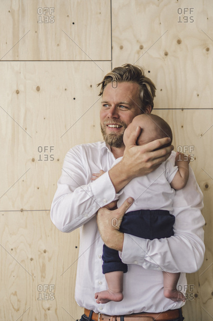 Working father standing in office- holding his son