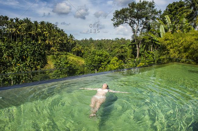 Indonesia- Bali- Ubud- Kamandalu Ubud resort- Woman enjoying the beautiful overflowing pool