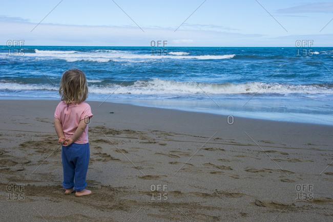 Spain- Canary Islands- Fuerteventura- La Pared- Playa del Viejo Rey- little girl standing on the beach