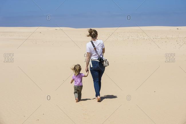 Spain- Canary Islands- Fuerteventura- Parque Natural de Corralejo- mother and daughter walking in sand dunes