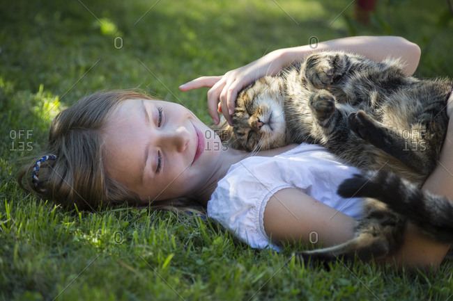 Girl lying with cat in garden