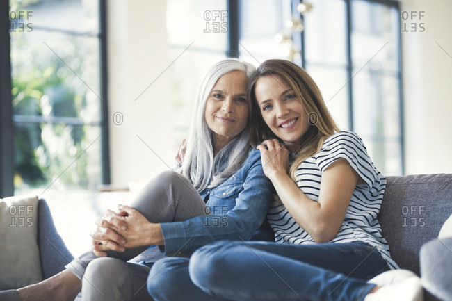 Daughter holding mother in her arms- sitting on couch
