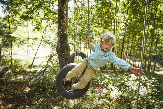 Boy balancing on tires at an adventure park in forest