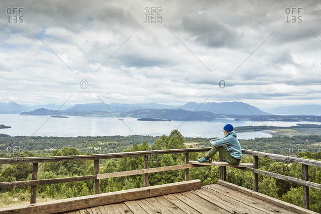 Chile- Puren- Nahuelbuta National Park- woman sitting on observation terrace overlooking the lake