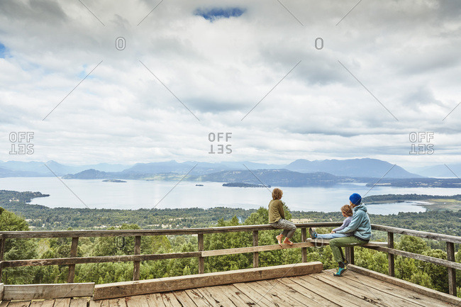 Chile- Puren- Nahuelbuta National Park- woman with two sons sitting on observation terrace overlooking the lake