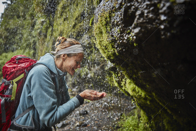 Chile- Patagonia- Osorno Volcano- woman refreshing with water from Las Cascadas waterfall