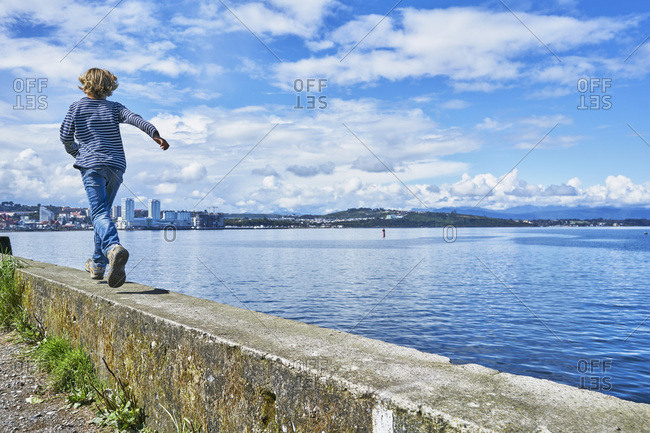 Chile- Puerto Montt- boy running on quay wall at the harbor
