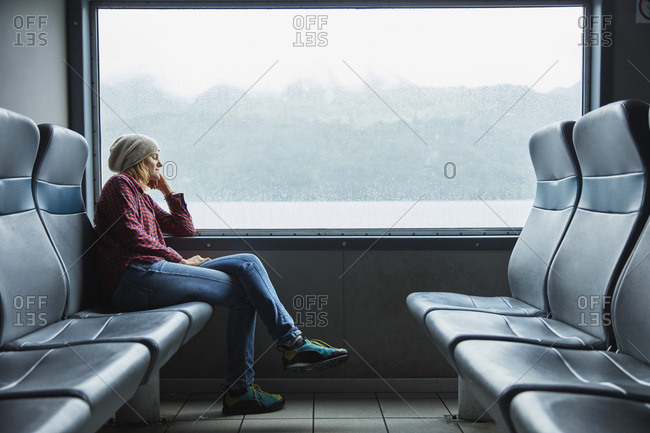 Chile- Hornopiren- woman sleeping at the window of a ferry