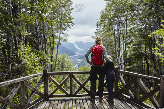 Chile- Chaiten- Parque Pumalin- mother and son on observation deck looking at glacier