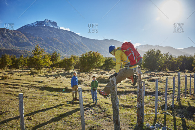 Chile- Cerro Castillo- mother with two sons on a hiking trip jumping over paddock fence