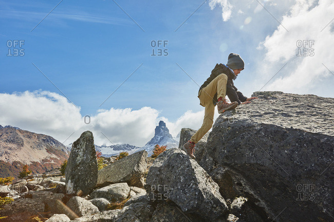 Chile- Cerro Castillo- boy climbing on rock in mountainscape