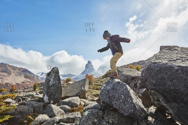 Chile- Cerro Castillo- boy jumping from rock in mountainscape