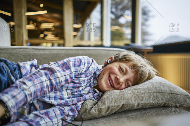 Happy boy lying on couch with earphones