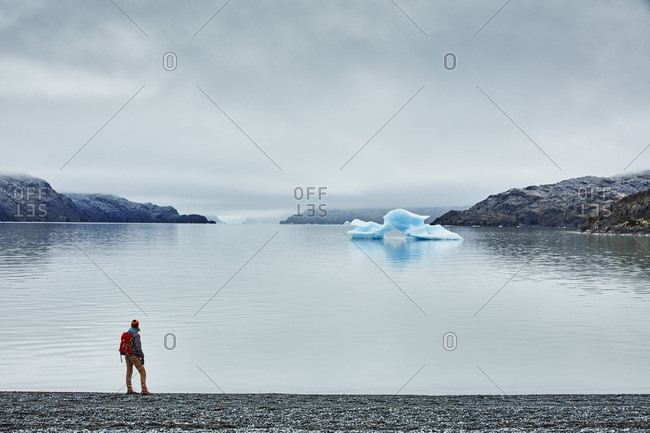Chile- Torres del Paine National park- Lago Grey- woman standing at the shore looking at iceberg