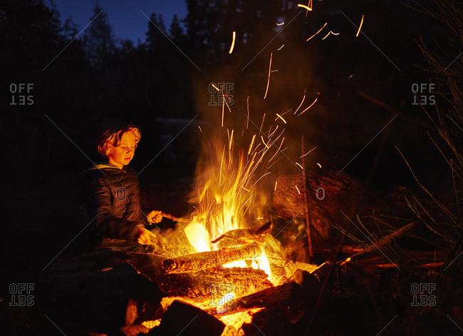 Argentina- Patagonia- Lago Futalaufquen- boy at camp fire at night