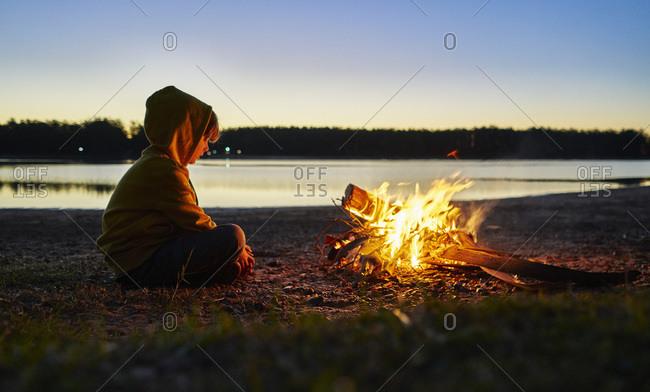 Argentina- Patagonia- Concordia- boy sitting at camp fire at a lake