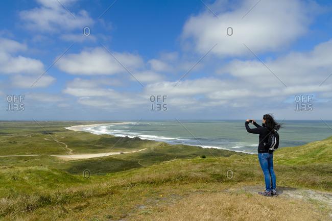 Denmark- Jutland- Bulbjerg- woman taking pictures in dune landscape