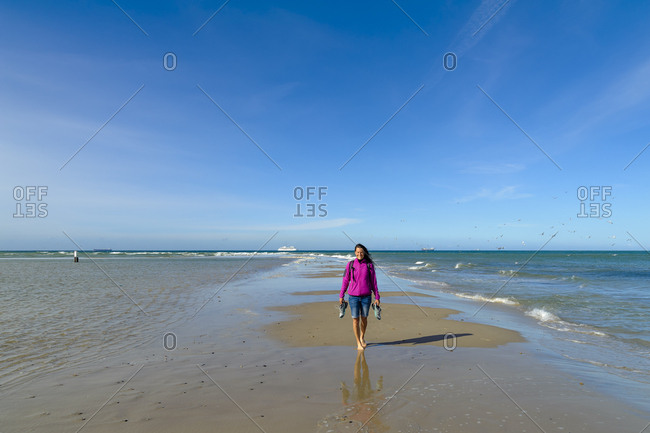 Denmark- Jutland- Skagen- Grenen- woman on the headland with North Sea and Baltic Sea