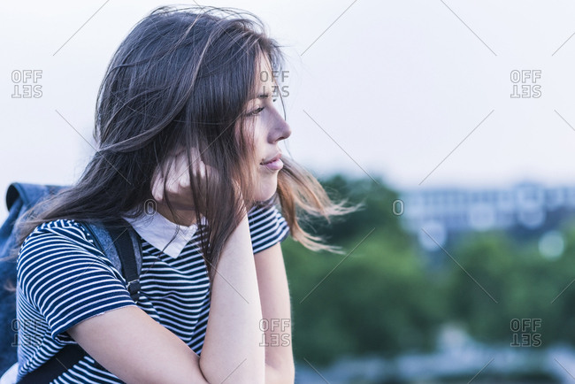 Pensive young woman with backpack leaning on railing