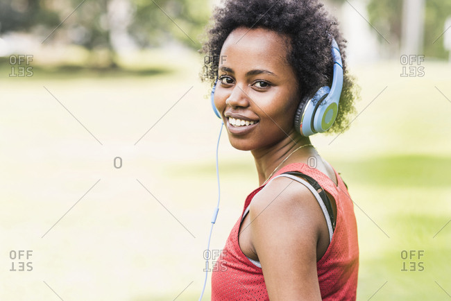 Portrait of smiling sporty young woman with headphones in park