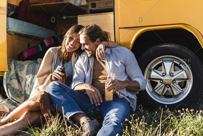 Affectionate couple on a road trip- taking a break- drinking soft drinks