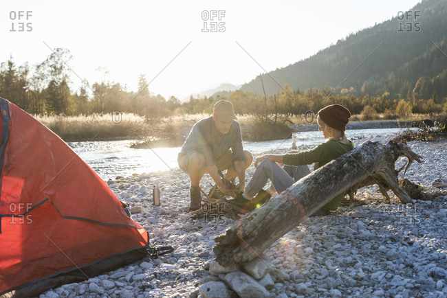 Mature couple camping at riverside- collecting wood for a camp fire