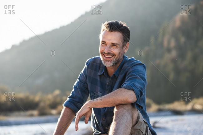 Mature man camping at riverside