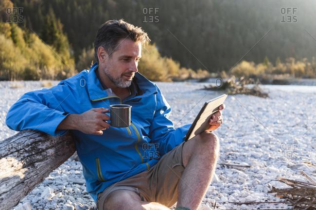 Mature man camping at riverside- using tablet