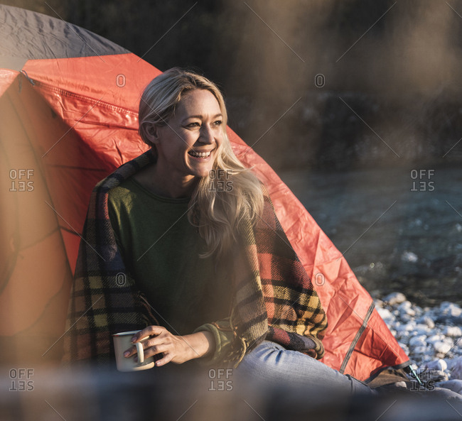 Mature woman camping- sitting in front of tent
