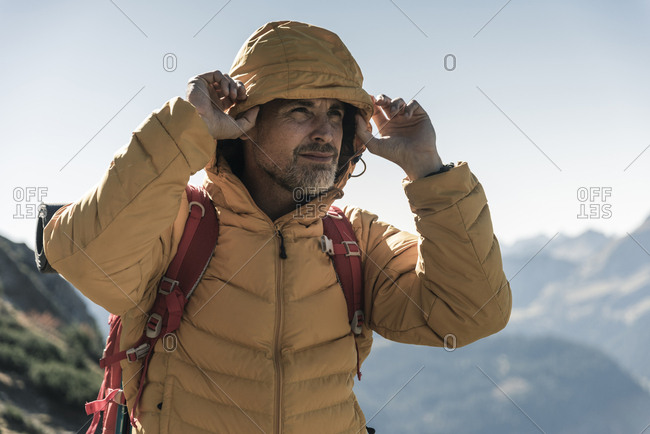 Austria- Tyrol- portrait of man with hooded jacket on a hiking trip in the mountains