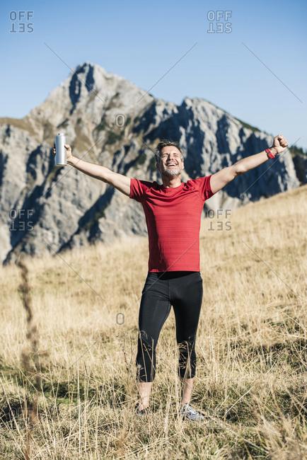 Austria- Tyrol- happy athlete standing on alpine meadow