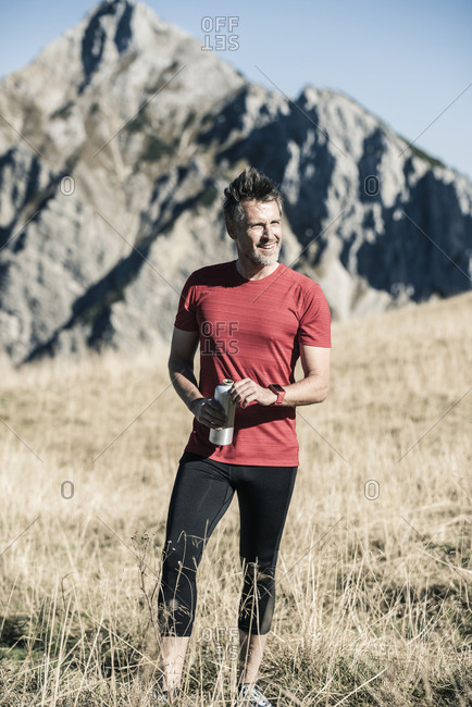 Austria- Tyrol- smiling athlete standing on alpine meadow