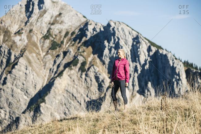 Austria- Tyrol- smiling female athlete standing on alpine meadow