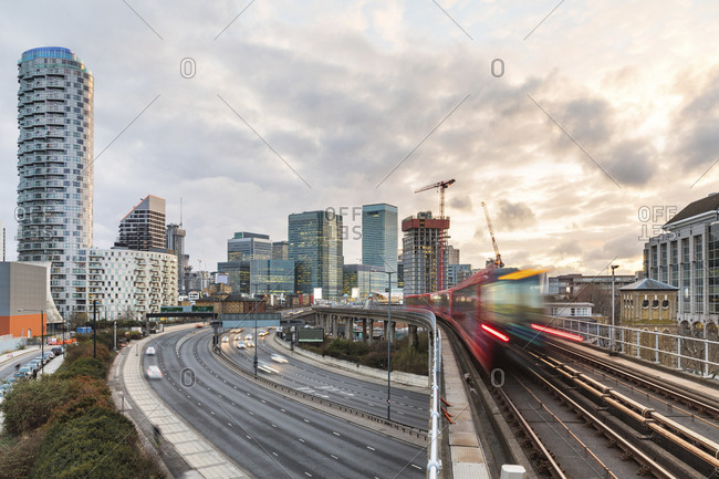 United Kingdom- England- London- financial district with busy road and blurred metro train on foreground