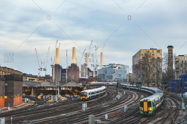 United Kingdom- England- London- view of railtracks and trains in the evening- former Battersea Power Station and cranes in the background